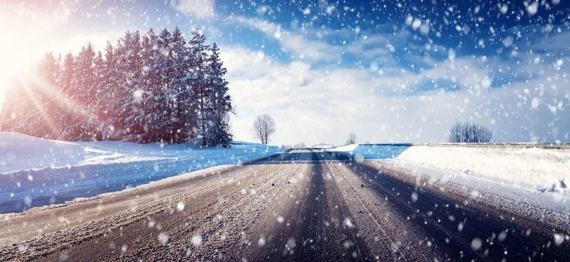Schneefahrbahn mit Sonnenschein und Schneefall